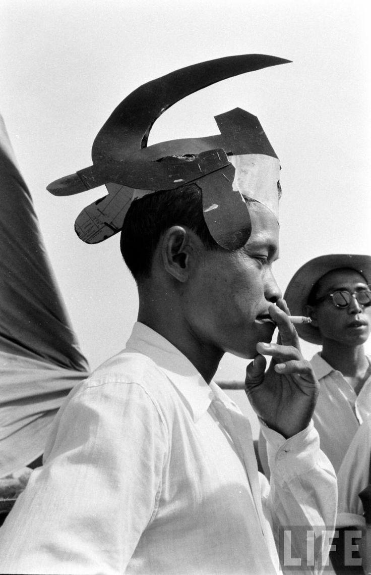 Pendukung PKI mengenakan tutup kepala berbentuk Palu Arit berwarna merah, September 1955