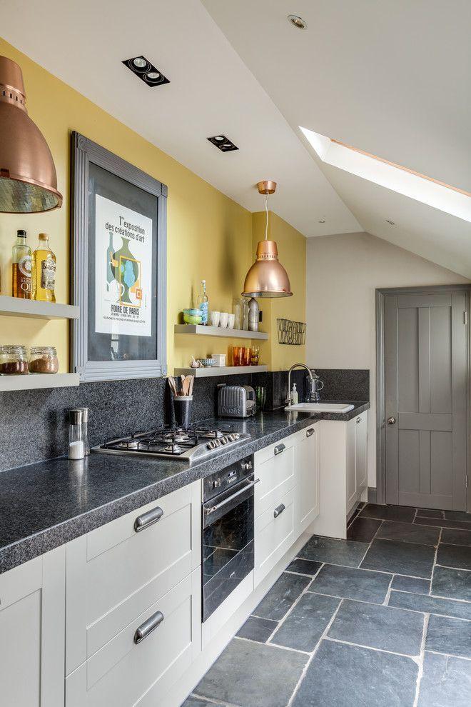 Серая кухня в интерьере: 75+ избранных классических и современных дизайнерских решений http://happymodern.ru/seraya-kuxnya-v-interere-foto/ Серо-желтая кухня. Серый цвет в интерьере: кухонный фартук, столешницы, двери, бытовые приборы. Центральная стена оформлена желтым цветом. Медный цвет абажуров – дополнительный цвет, поддерживающий желтый в интерьере современной кухни