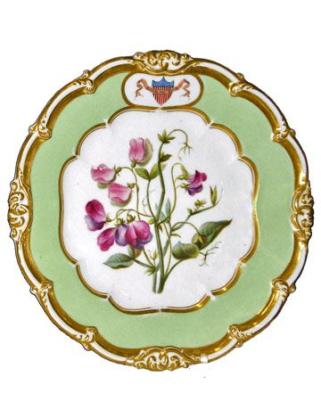 This rare Polk State Service dessert plate has an elegant sweet pea and violet floral motif.    President James K. Polk's china was the first to be designed with a shield of stars and stripes. Designs usually featured the Federal eagle motif.    VALUE = $25000