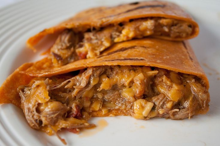 Slow Cooked Beef and Mango Quesadillas    2 lbs top of the round beef roast    1 cup barbecue sauce    4 large whole wheat tortillas    1 large mango, peeled and thinly sliced    1 small red onion, very thinly sliced    1 cup sharp cheddar cheese