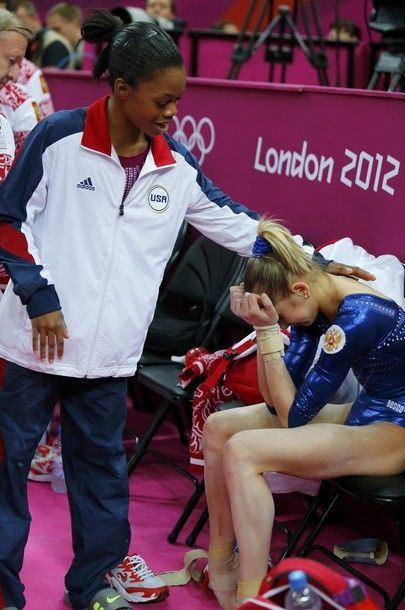 Gold medallist Gabby Douglas of the U.S. comforts silver medallist Victoria Komova of Russia after the women's individual all-around gymnastics final in the North Greenwich Arena at the London 2012 Olympic Games August 2, 2012.