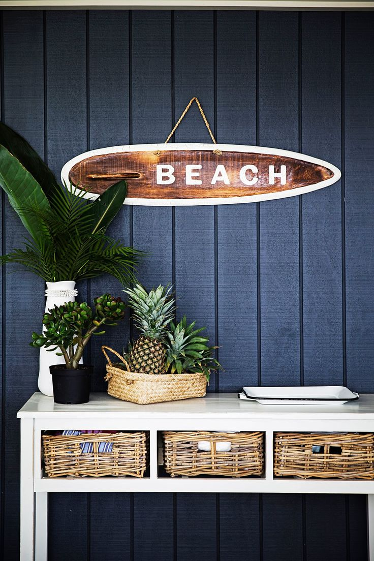 beach style entry with navy wood panels, white table with baskets as drawers…