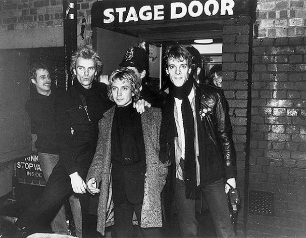 18th December 1979: The pop group Police outside the stage door of a Hammersmith venue in west London, with a policeman standing behind them. From left to right, they are Sting, Andy Summers and Stewart Copeland. Photo: Martyn Goddard, Getty Images / Getty Images 2011