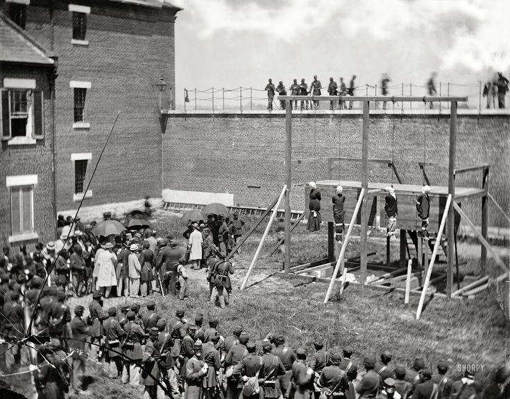 """Shorpy::  July 7, 1865. """"Washington, D.C. Hanging hooded bodies of the four conspirators; crowd departing."""" Lincoln assassination conspirators Mary Surratt, Lewis Payne, David Herold and George Atzerodt shortly after their execution at Fort McNair. Wet plate glass negative by Alexander Gardner."""