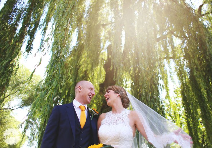 laughing bride in her wedding dress and groom on a sunny day with trees in the back ground in Manchester, UK