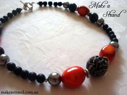 An acid-treated agate focal bead is flanked by orange coral and silver-grey shell pearls and brushed black agate (sold)