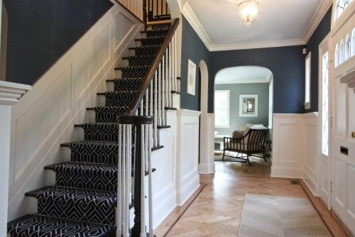 The walls are covered in a navy blue grasscloth wallpaper from Thibaut. A navy and white geometric patterned stair-runner, held in place with stair rods capped with pineapple finials, further contributes to the home's coastal feel.