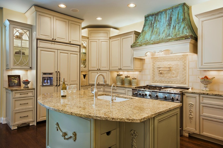 Love the verde green range hood and coordinating island base color with antiqued cream cabinets.    Frey Architecture