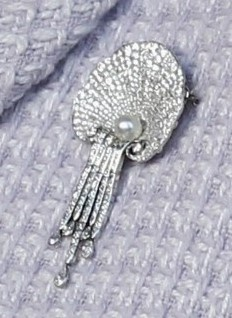 The Queen Mother's Shell Brooch (official name: the Courtauld Thomsen Scallop-Shell Brooch), was inherited by Queen Elizabeth from her mother, Queen Elizabeth, the Queen Mother. It takes the shape of a shell made of solid rows of diamonds with a single pearl cradled at the base and strings of diamonds of varying lengths suspended underneath.   The Queen Mother wore it often; most notably, she wore it during her 100th birthday celebrations.