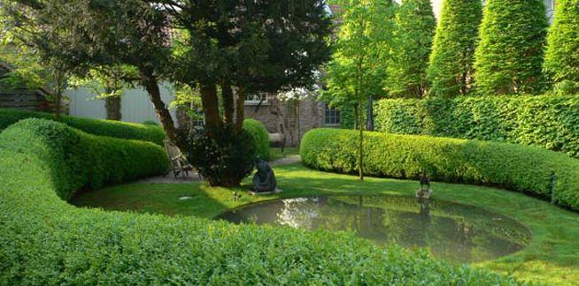 Wirtz tuinarchitectuur - Tuinontwerp Brugge  Als verwoede verzamelaars van moderne kunstwerken wilden ze een wintergroene stadstuin die het huis verlengde, om zo de kunstwerken in hun tuin te kunnen tonen. Een verhoogde, weerspiegelende vijver, omringd door een buxushaag, reflecteert het water in de serre aan de rechterkant. Vanuit deze rechthoekige vijver geven vloeiende buxushagen, die rond bestaande taxusbomen bewegen, de tuin meer diepte.