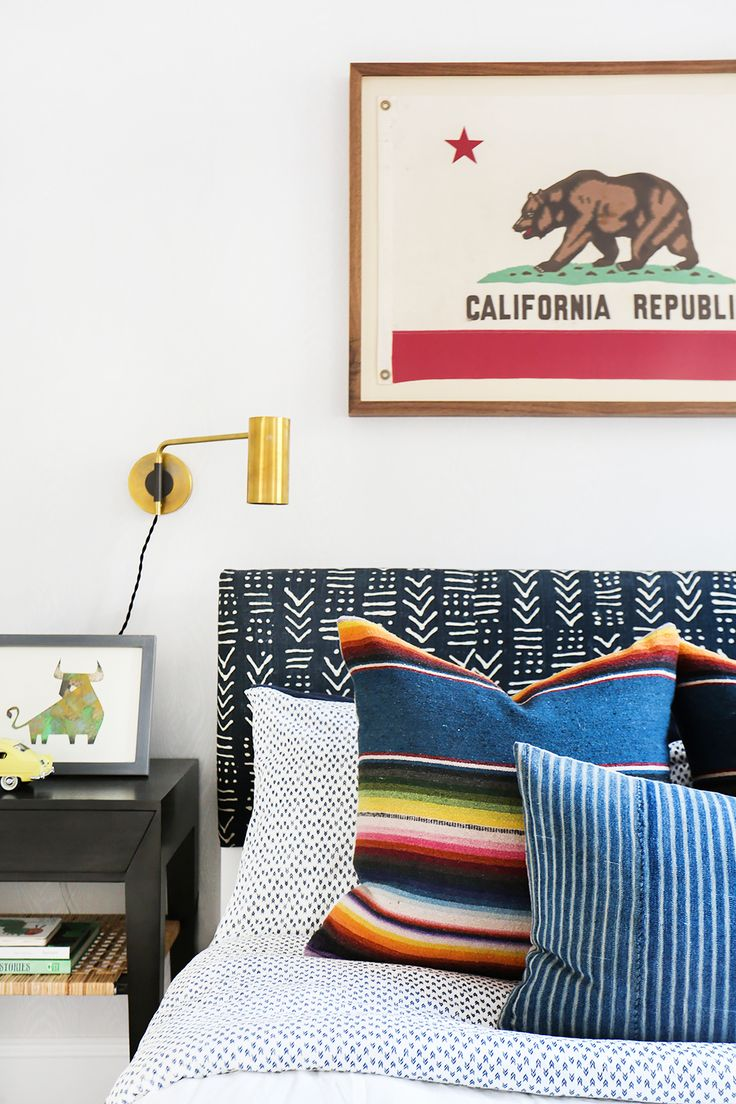 A cool young boy's room with patterned pillow, framed California flag and gold wall sconce
