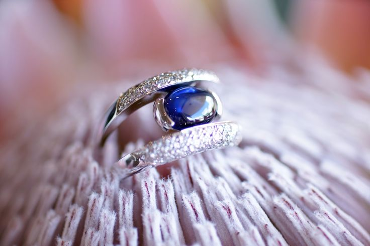AFTER We split the diamond bands, inlaid a half bezel setting and set a natural blue Australian cabochon cut sapphire to create a new ring.