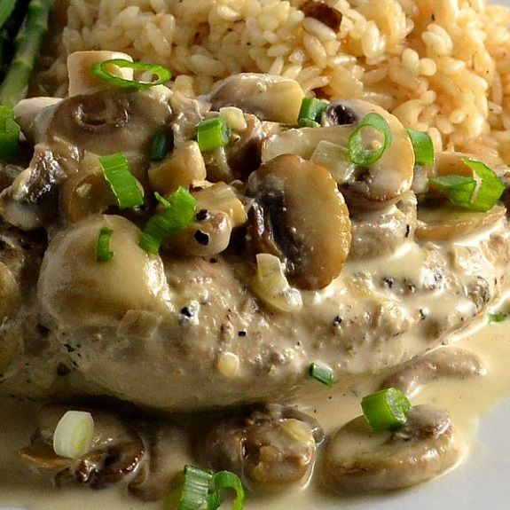Slow cooker chicken in mushroom-wine sauce. Chicken breasts with fresh mushrooms,dry white wine and cream of chicken soup cooked in slow cooker.