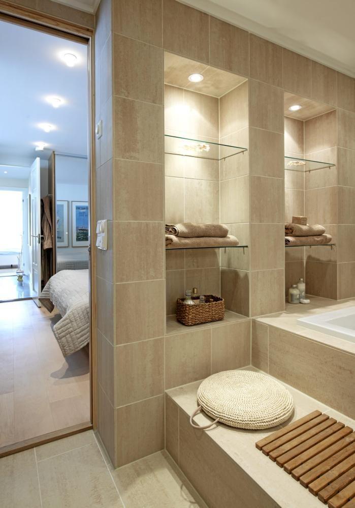 Badet innenfor foreldresoverommet er kledd med granittfliser fra Flisekompaniet. B�de hyller og badekaret fra Porsgrunn Porselen er innebygd. Foran badekaret er det laget en praktisk sittebenk.