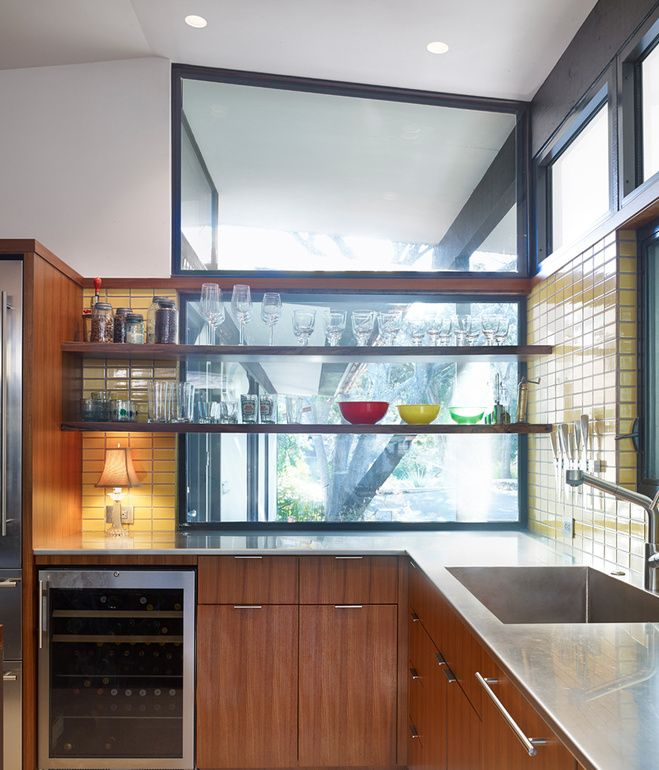 Opening the kitchen to outdoor spaces, a new window with floating shelves for storage looks out into the front yard.  New appliances, sta...