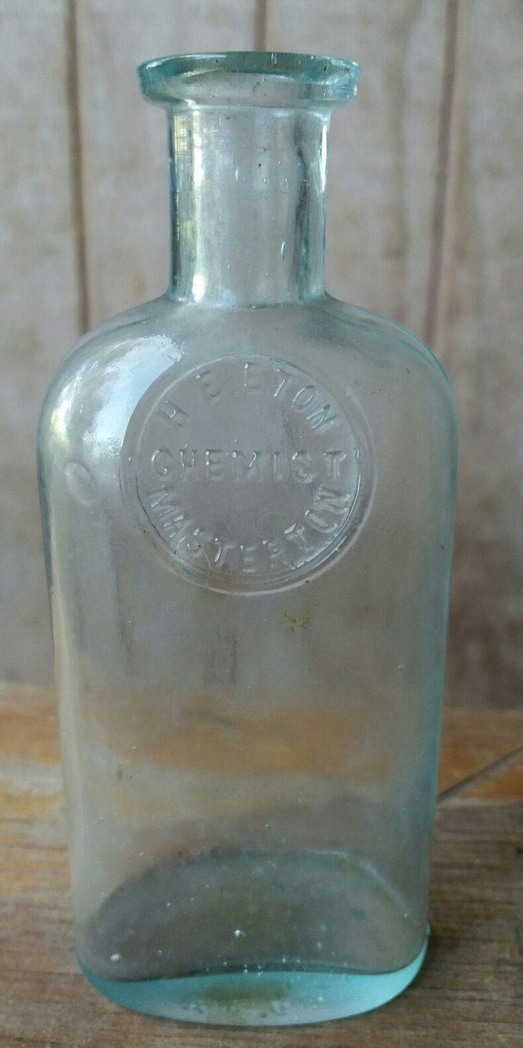 H. E. Eton Chemist Masterton. Oval section bottle with embossing in circular style like an applied seal. Aqua 13cm.