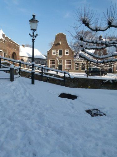 De Grote Spui in wintersfeer, gezien vanaf de Kleine Spui. Op de voorgrond een klassieke lantaarn. Links is de stadszijde van de Koppelpoort gedeeltelijk zichtbaar.