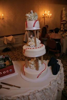 three tier baseball bat wedding cake featuring a baseball rose in the center of each tier.