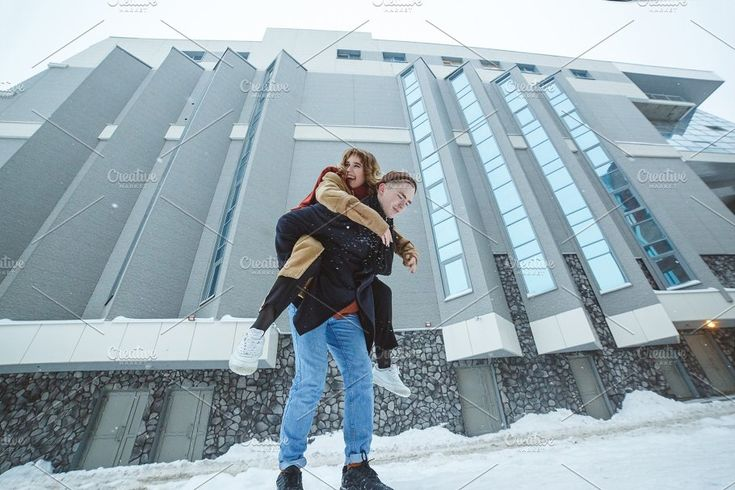 Active young couple running, jumping and enjoying together in winter city background by Northern Life on @creativemarket