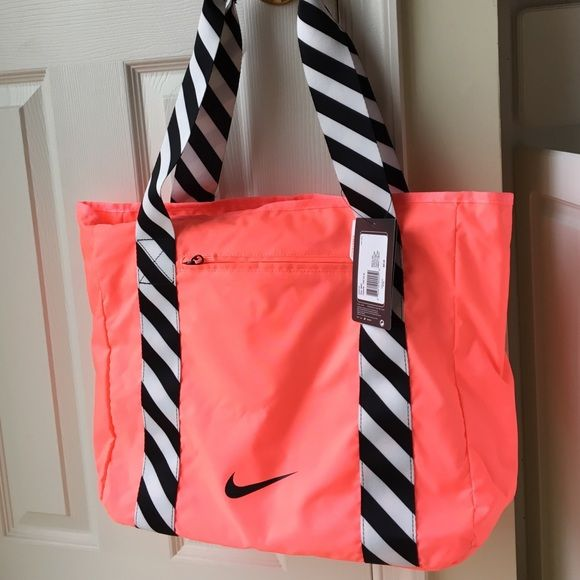 NWT Bright Coral NIKE bag NWT Bright Coral NIKE bag w/black &white stripe should straps. 1 zip compartment on inside and 1 on the front. Could be used as a beach bag or a gym bag. Nike Bags