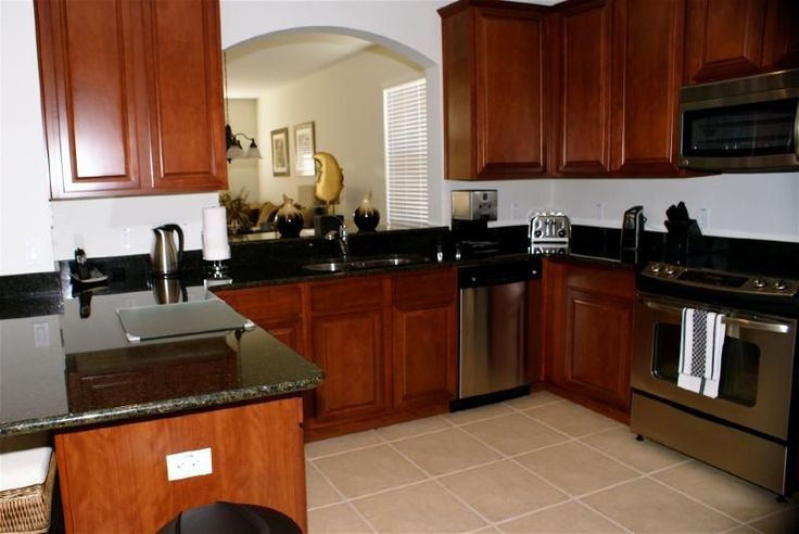 Cherry wood kitchen cabinets with black granite cherry for Cherry wood kitchen cabinets