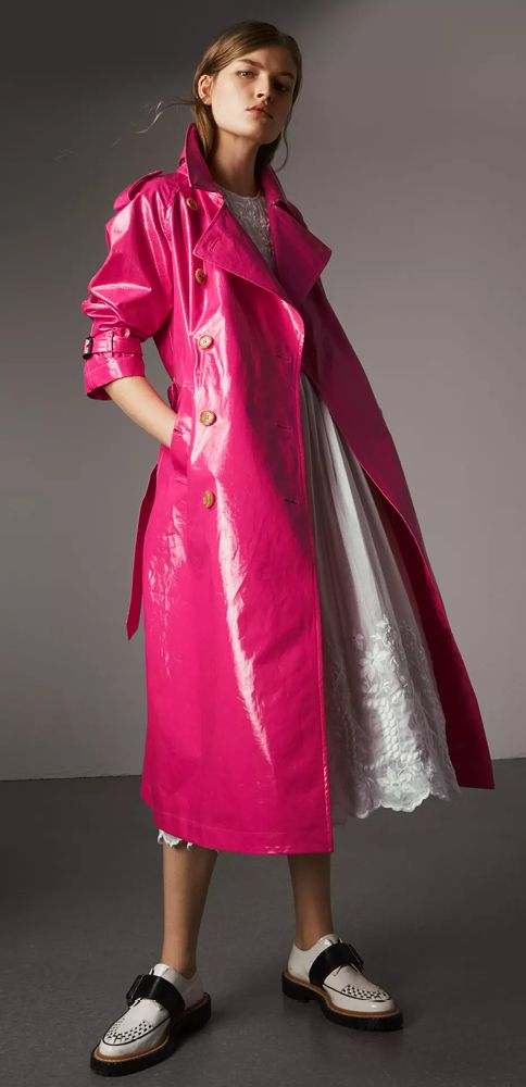 A classic Burberry trench reworked in a high-gloss laminated cotton in a vibrant neon tone. The relaxed cut features a pronounced storm shield for volume. Layer with silks and lace to create unexpected contrasts.