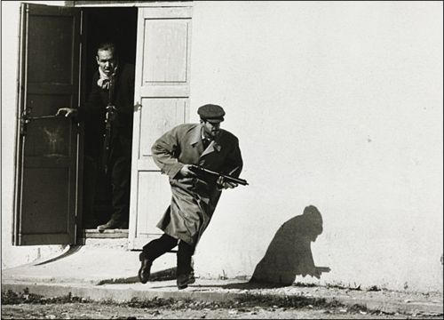 Turkish Cypriot sprinting from a cinema door under fire, Limassol, Cyprus, Don McCullin 1964