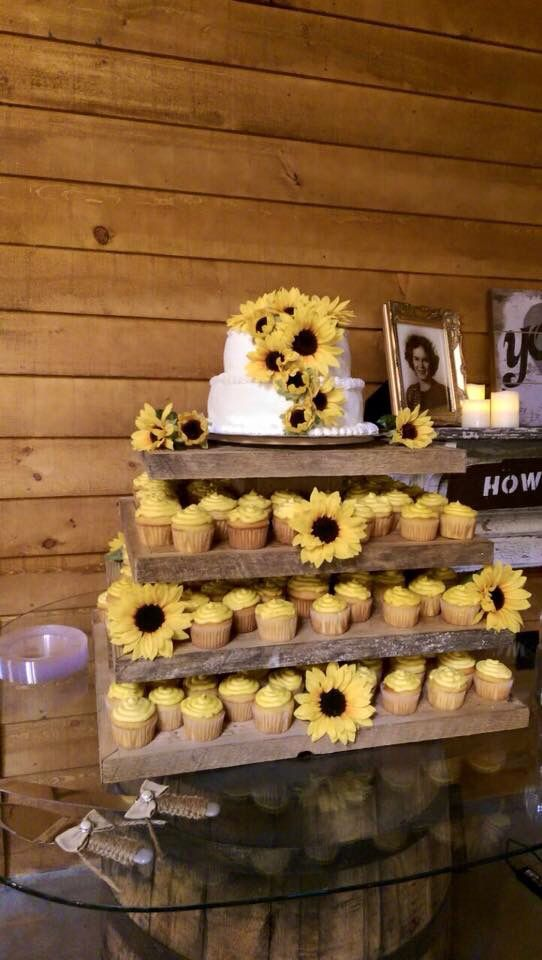 2 Layer Sunflower wedding cake with 125 cupcakes. Round glass top on whiskey barrel.  6.20.15 Abbott Wedding at Crosslink Meadows Farm in Forsyth,Georgia