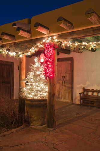 Christmas decorations and tree on an adobe porch, Santa Fe, New Mexico.