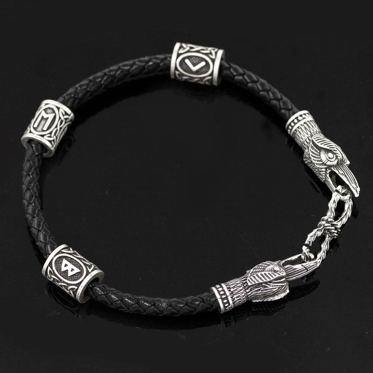 Huginn & Muninn Leather Bracelet. This Raven bracelet is the result of unique craftsmanship, it features two raven heads biting onto a ring with three rune beads attached to it. This bracelet is made from genuine leather and solid stainless steel. Find out more at pagan-revival.com! #norse #jewelry #ancient #bracelet