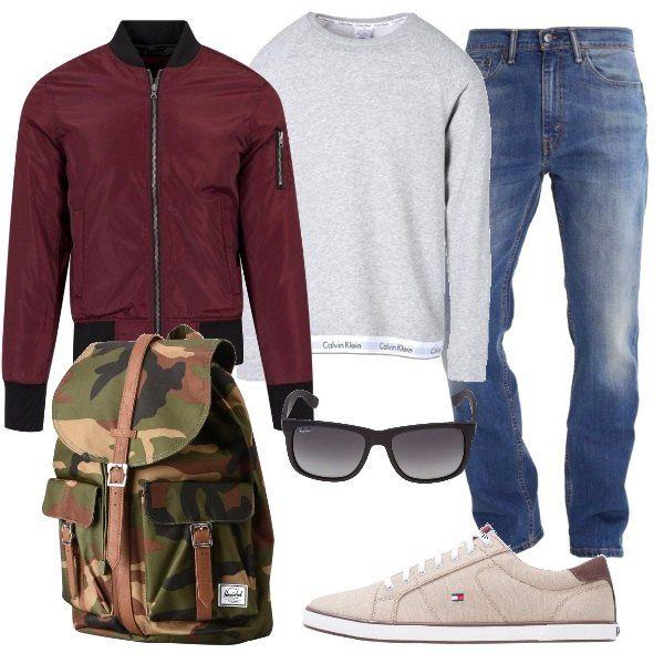 L'outfit è composto da un bomber color burgundy in poliestere con zip, la felpa Calvin Klein con logo sul fondo ed un paio di jeans leggermente slavati Levi's. Completano il look le sneakers basse Tommy Hilfiger, gli occhiali da sole scuri Ray-Ban e lo zaino in fantasia mimetica con tasche esterne.