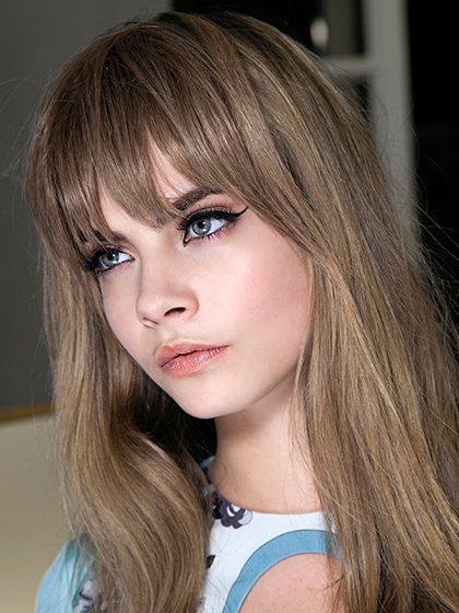 Cara Delevingne with bangs, rosy cheeks and a cat eye | allure.com