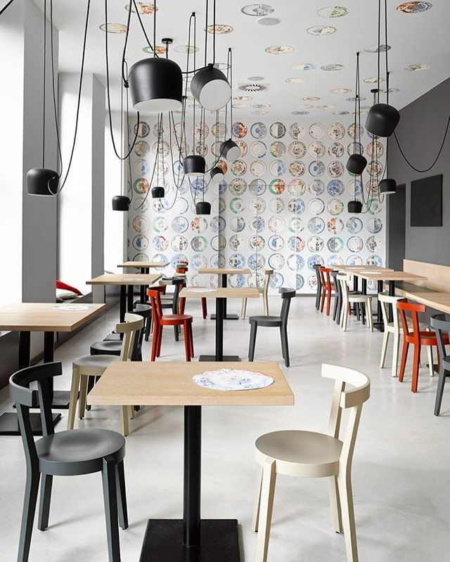 Unevenly hung @flos_usa Aim pendants and mismatched wooden chairs create  whimsy within this Prague bistro