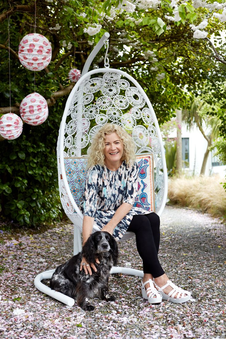 Carolyn at home with her dog Maddie on a white outdoor chair with hanging Japanese-inspired lanterns. All items by Carolyn Donnelly eclectic