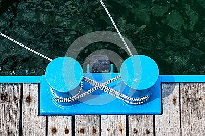 Two blue metal bollards with rope on a wooden jetty near water.