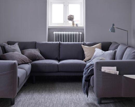 Séjour avec canapé 8 places gris foncé en U, avec pieds gris.