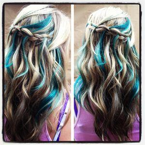 Blonde hair with teal lowlights; wavy hairstyle; waterfall braid