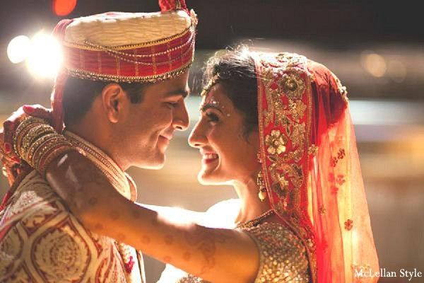 An Indian bride and groom pose for portraits at their wedding.