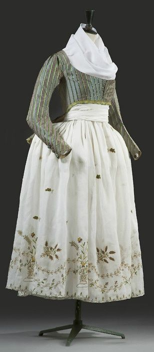 "A ""Macaroni"" Jacket and an Embroidered Skirt: ca. late 18th century, French, jacket of two-tone silk and satin with silk fringed fronts and bustle, the cuffs with silk-covered buttons, lined with patch work of silk brocades in the French manner, skirt  has a border of embroidered flower-filled urns."