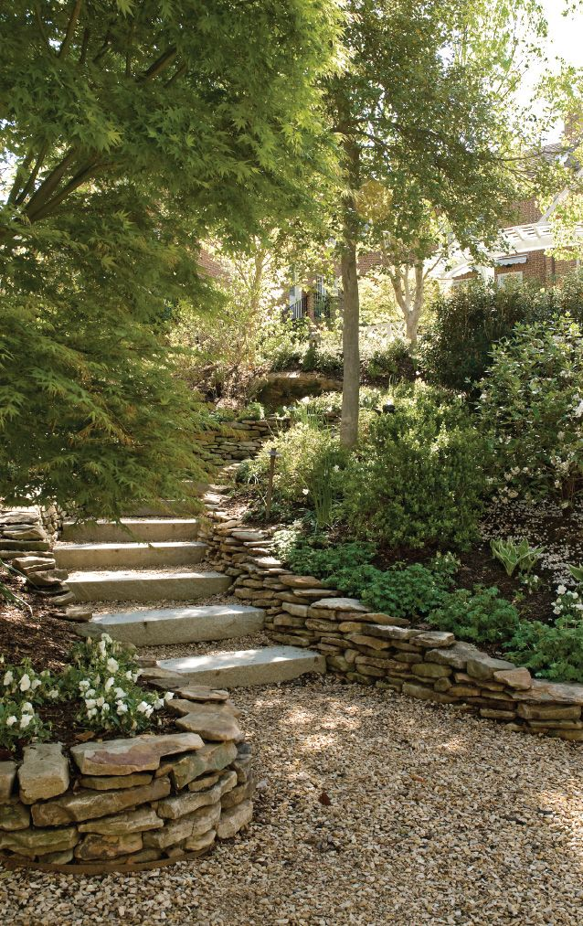 Retaining walls specifically designed to recreate the look of stacked rock walls line the steps leading down to a secluded sitting area.