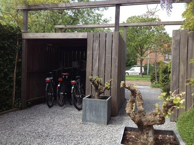 Fietsenberging naast het huis + tuinhuis eraan en grote trellis erboven voor groene slingerplant als druif/winde/klimop
