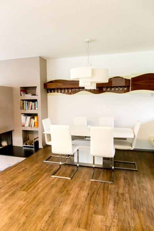 Inbuilt shelving around fireplace and wall shelving for glasses in dining area.