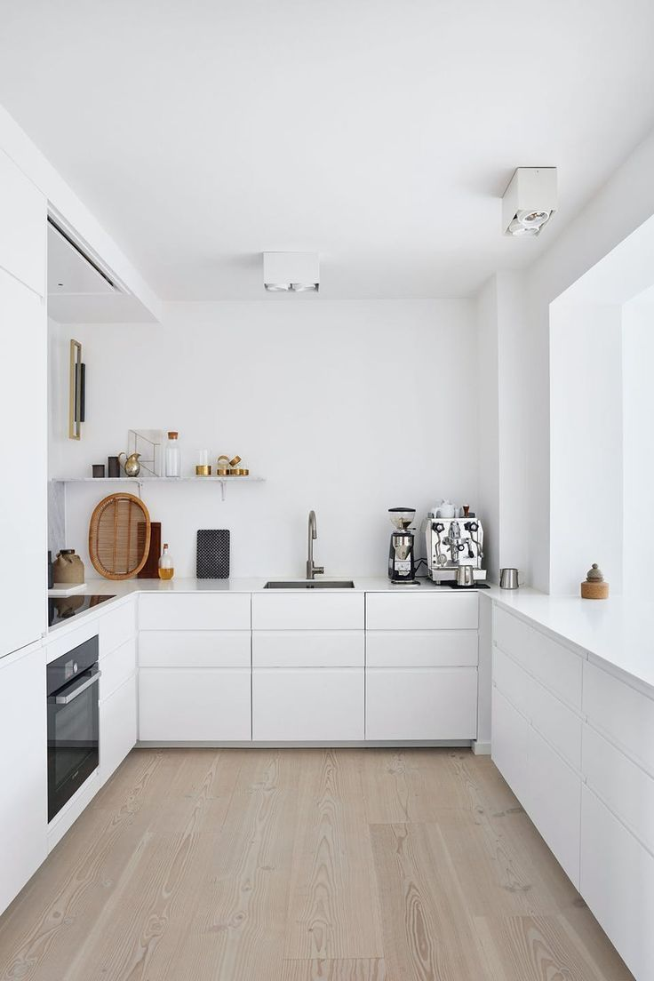 This elegant and white kitchen is decorated with IKEA furniture and a profi …