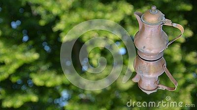 Metal, rusty, small pitcher on a green background with reflections of the sky.