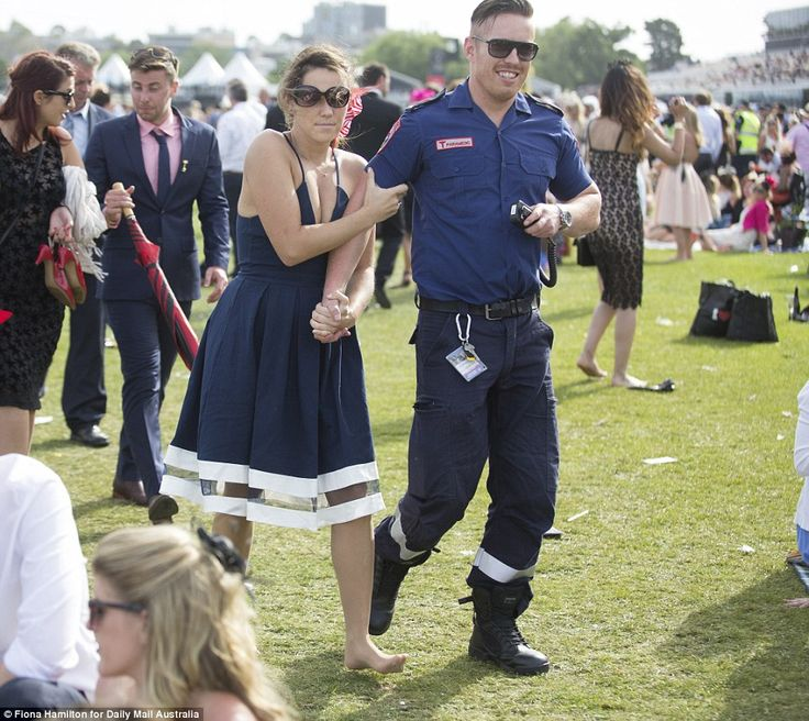 A barefoot woman in a navy dress with white trimming locked fingers with a paramedic who smiled as he guided her through the bustling crowd on Tuesday afternoon