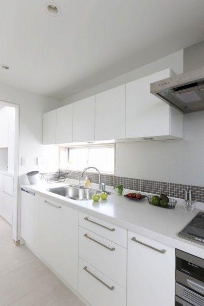 壁に貼ったグレーのモザイクタイルは、その色合い、貼る高さなどをとことん吟味、真っ白いキッチンをスタイリッシュに仕上げています。