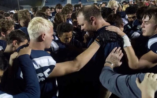 Atheists target HS football coach seeming to pray with players-but district apparently isn't caving