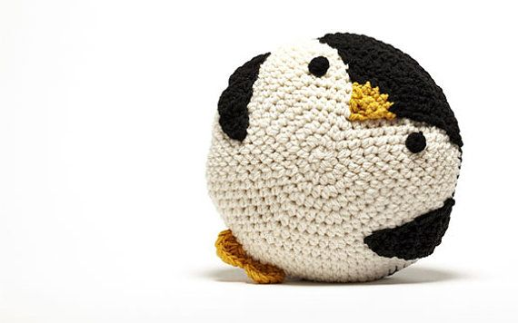 A cute and cuddly crocheted penguin pillow.