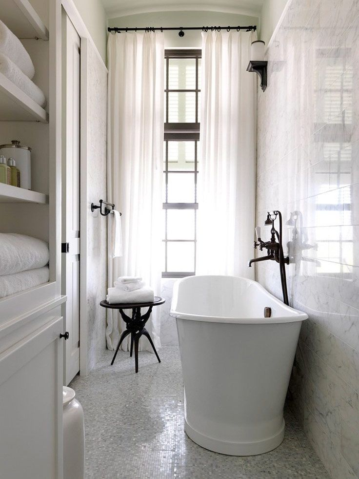 You can fit a bathtub even in a very narrow space. Whiteness all around with dark fixtures to bring contrast