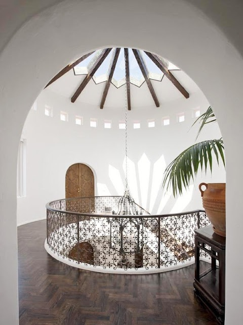 A stunning glass cathedral ceiling from the second floor landing with its Moorish ironwork railing and herringbone wood floors